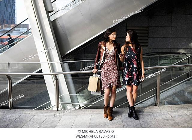 Two young women with shopping bags and cell phone in the city