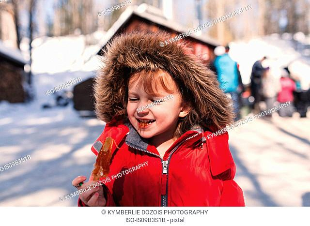 Girl in fur hood eating sticky lolly