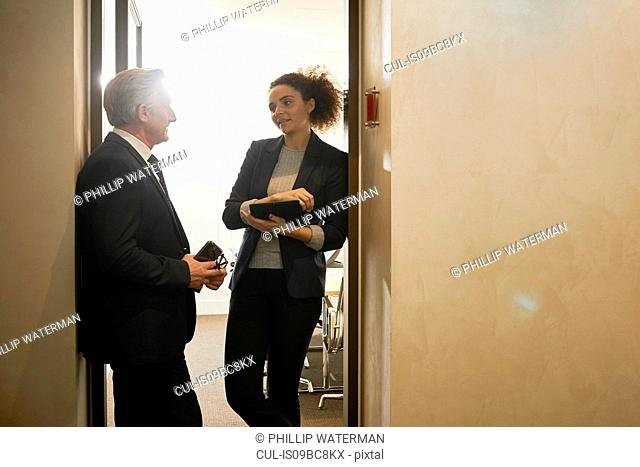 Businessman and woman talking in office doorway