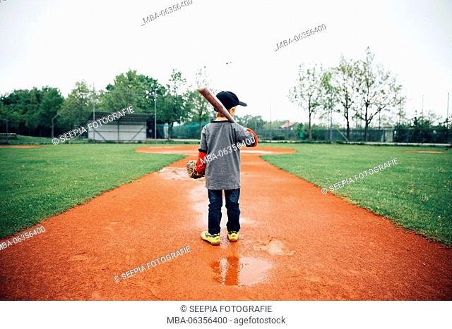 Boy, 5 years old, play baseball on a sports field in the rain, determination, training with ball, racquet and baseball glove, deep colours, focused, centred