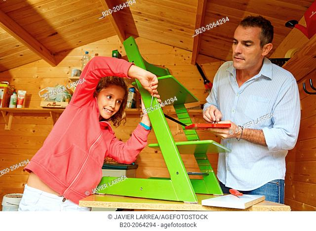 Father and daughter doing DIY. Assembling a chair