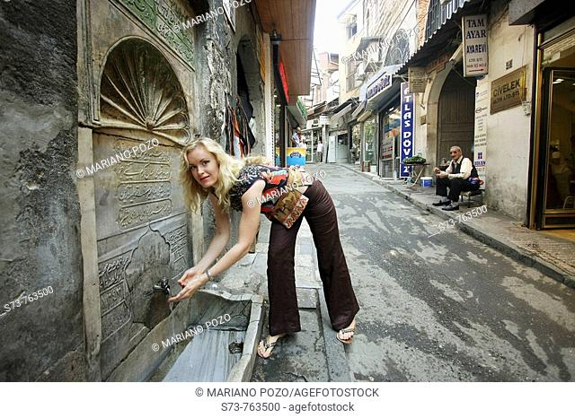 30 year old woman refreshing herself at fountain by the Gran Bazaar, Istanbul, Turkey