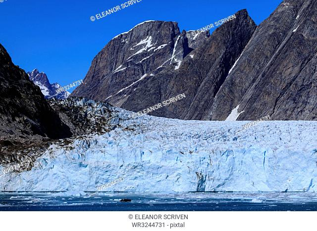 Cruise passengers in zodiac give scale to huge face, Thryms Glacier, Skjoldungen Fjord, glorious weather, remote East Greenland, Denmark, Polar Regions