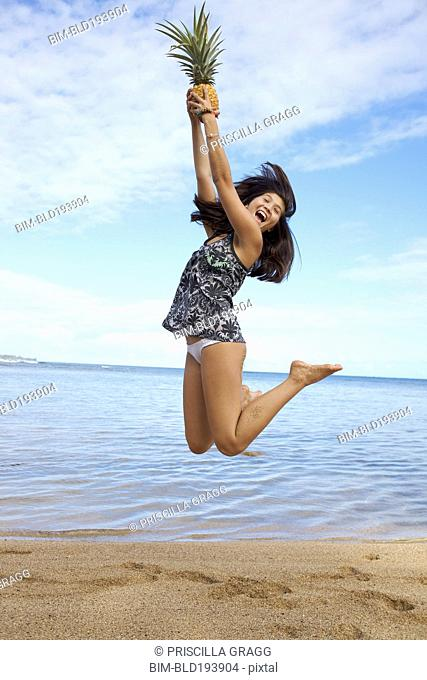 Mixed race teenager jumping and holding pineapple on beach