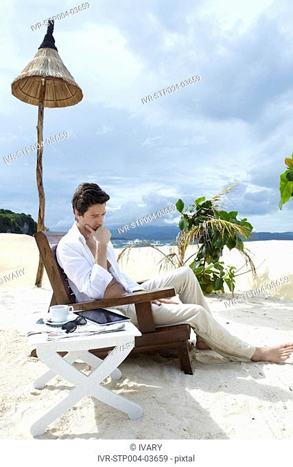 A man sitting in a deck chair at a resort