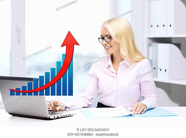 business, people, statistics and technology concept - smiling businesswoman with laptop computer, papers and growing chart sitting in office