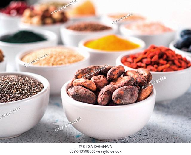 Raw cocoa bean in small white bowl and other superfoods on background. Selective focus. Different superfoods ingredients