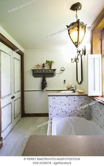 Main bathroom with bathtub encased in ceramic base and medieval style pendent lighting fixture inside an old 1892 Canadiana cottage style home