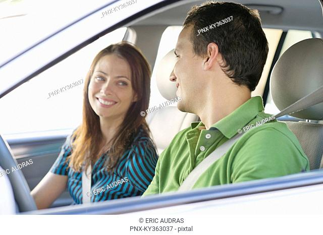 Happy couple looking at each other while driving a car