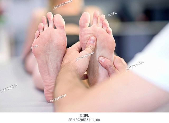 Person massaging woman's feet