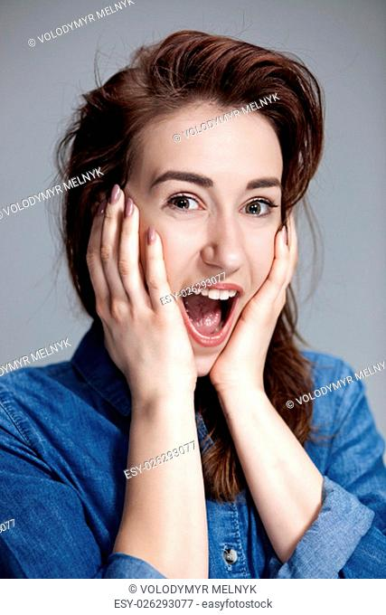 Portrait of young woman with shocked and surprised facial expressions over gray background