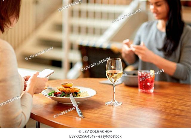 food, new nordic cuisine, technology and people concept - women with smartphones having breaded fish fillet with tartar sauce and oven-baked beetroot tomato...