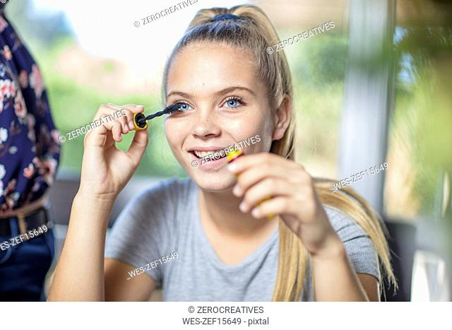 Portrait of smiling teenage girl applying mascara
