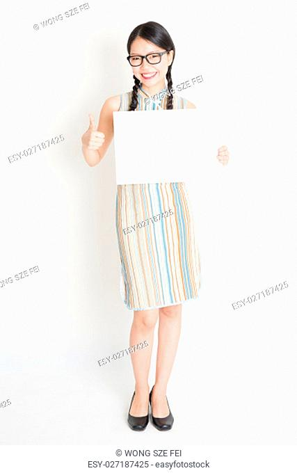 Portrait of young Asian girl in traditional qipao dress hand holding white blank paper card and giving thumb up, celebrating Chinese Lunar New Year or spring...