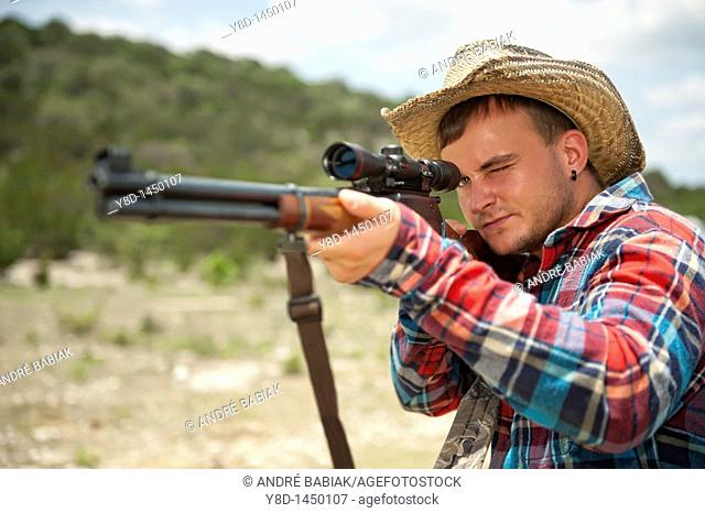 Hunting season in America - Man with cowboy hat shooting a rifle