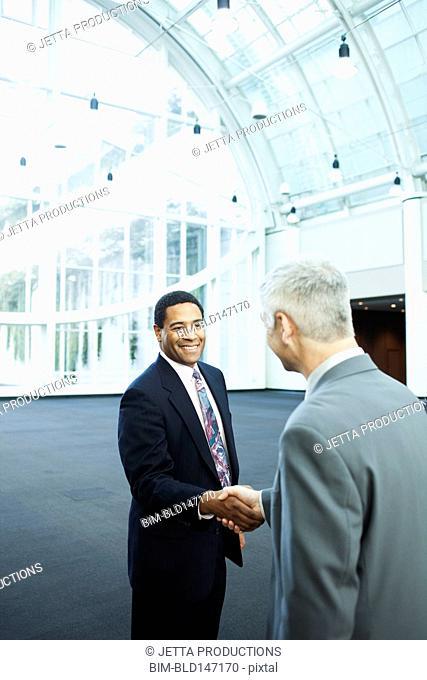 Businessmen shaking hands in lobby