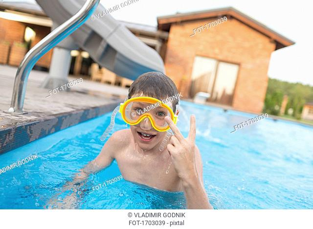 Portrait of shirtless boy showing peace sign while swimming in pool