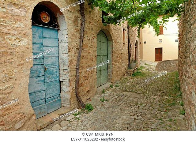 picturesque paved stone alley in italian old small town , Spello