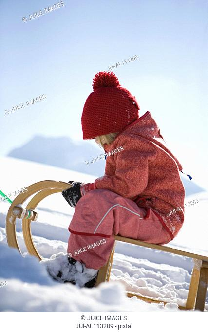 Girl sitting on sled in snow