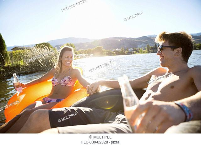 Young couple holding hands drinking water in inflatable rafts on sunny summer lake