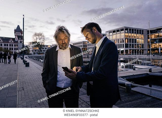 Two businessmen with cell phone at city harbor at dusk