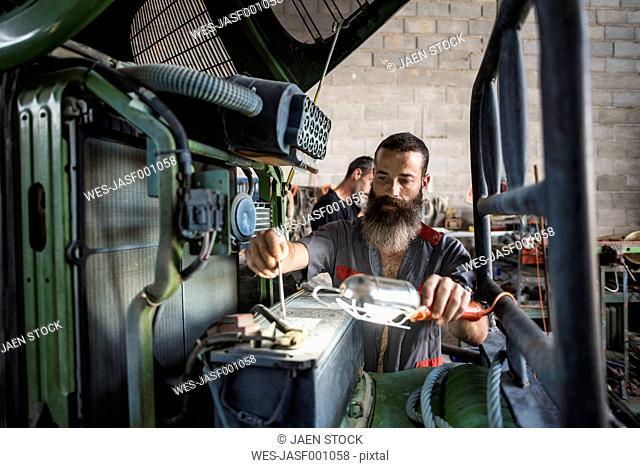 Mechanic repairing tractor