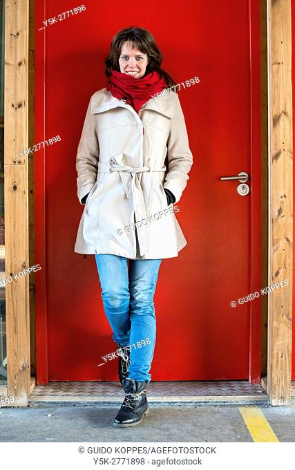Tilburg, Netherlands. Portrait of a young adult caucasian woman leaning against a red colored door at down town former Railway Zone