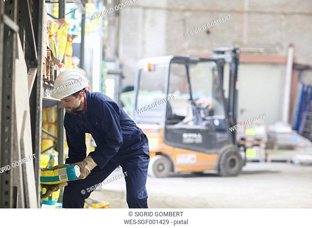 Warehouseman in storehouse lifting sack