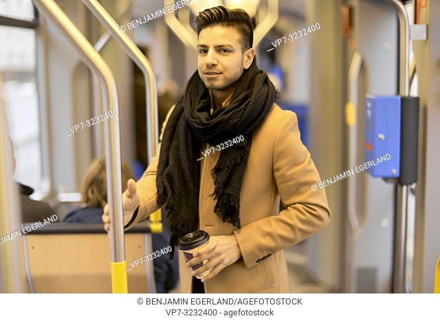 young man in train, public transport, in Munich, Germany