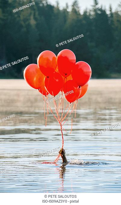 Hand in water holding bunch of red balloons