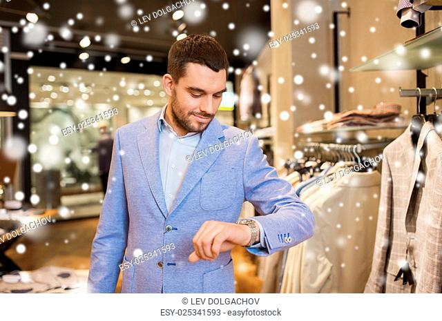 sale, shopping, fashion, style and people concept - happy young man in jacket looking at wristwatch at clothing store over snow