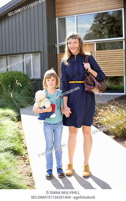 Mother with daughter (6-7) in front of modern house