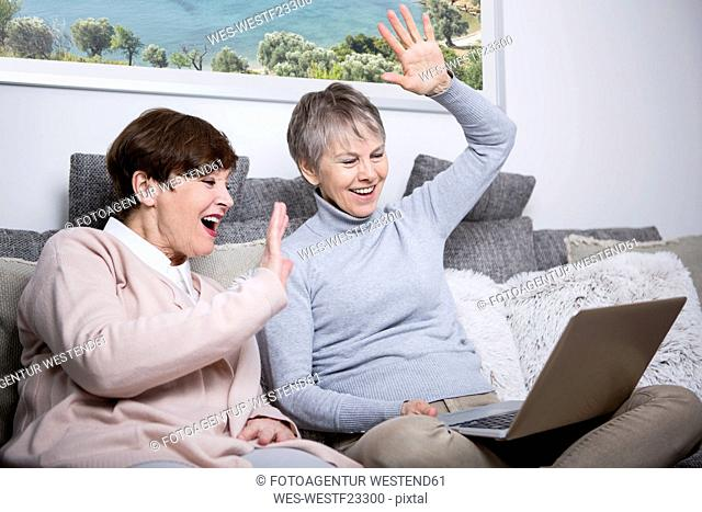 Two senior women sitting on couch, watching laptop