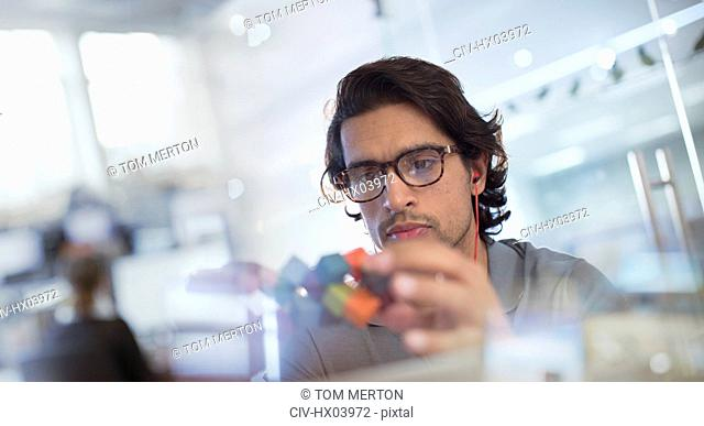 Focused, innovative male entrepreneur examining prototype in office