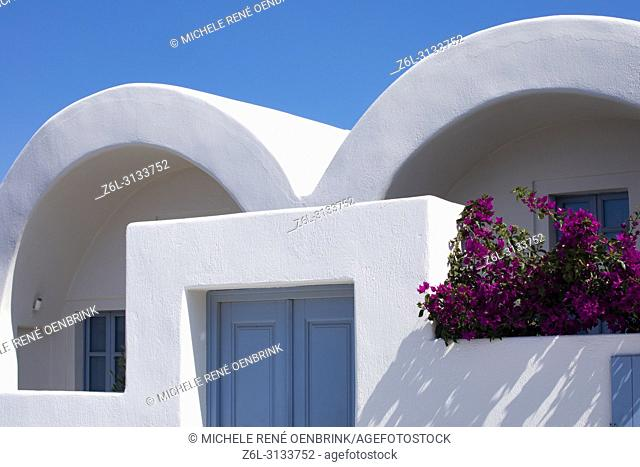 Traditional Greek architecture cave home with pink bougainvillea flowers and blue windows in Oia, Santorini Greece