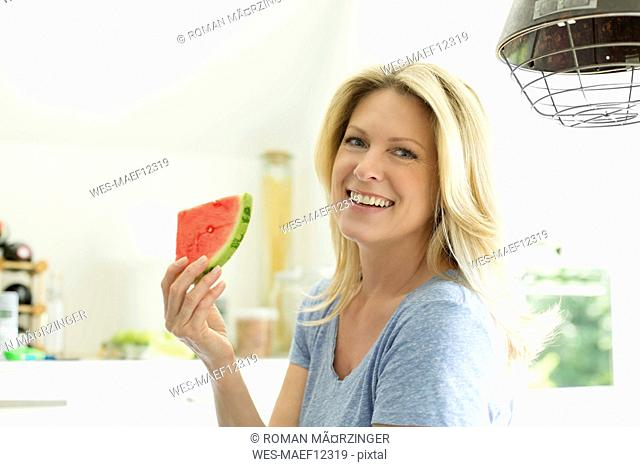 Mature woman sitting in kitchen, eating water melon