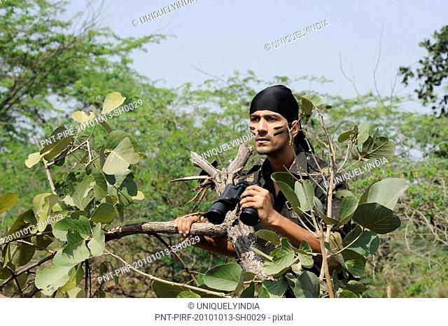 Soldier holding binoculars in a forest