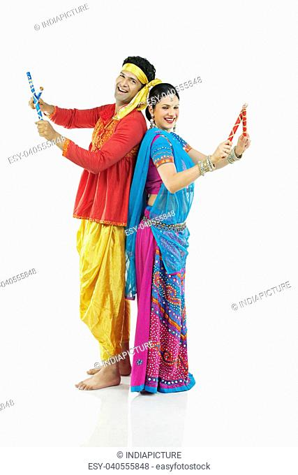 Gujarati couple performing dandiya dance