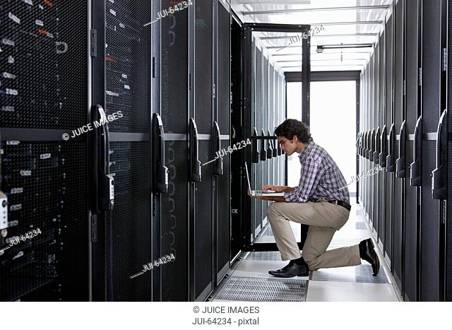 Technician, kneeling with laptop, checking aisle of server storage cabinets in data center