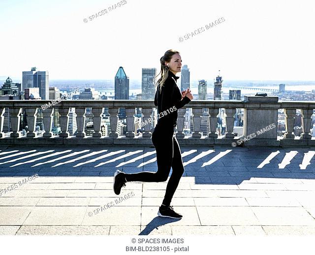 Caucasian woman running in city
