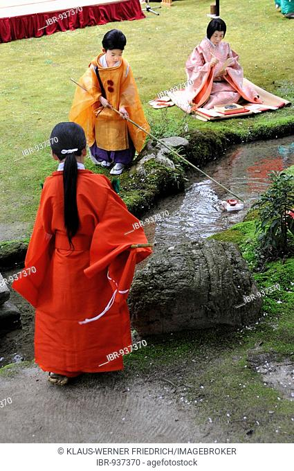 Girl in kimono of the Heian period steering a floating wooden duck with a Sake bowl in the Kamigamo Shrine in Kyoto, Japan, Asia