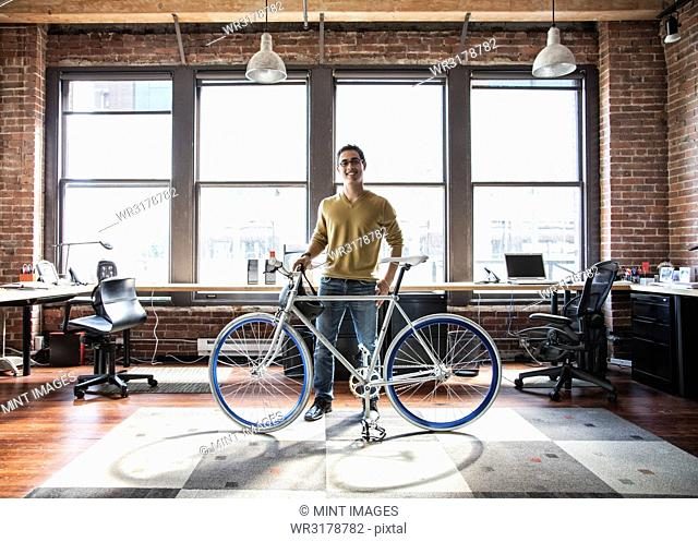 Hispanic man at his office workstation with a bicycle