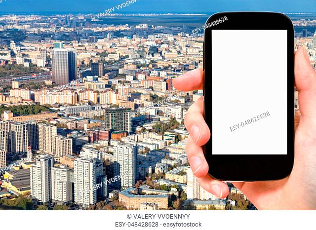 travel concept - tourist photographs of aerial view of northeast of Moscow city from observation deck in autumn on smartphone with empty cutout screen with...