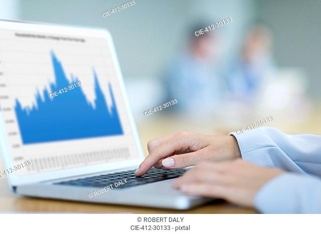 Close up of businesswoman using laptop in conference room