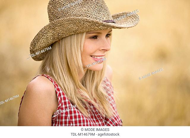 A portrait of a woman wearing a cowboy hat outdoors, smiling