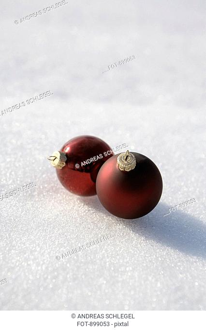 Two Christmas ball ornaments on the snow