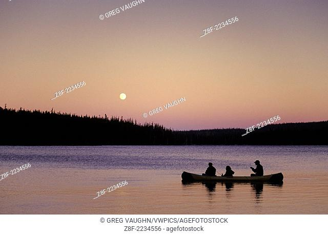 People fishing in canoe with full moon rising, Olallie Lake, Mt. Hood National Forest, Cascade Mountains, Oregon