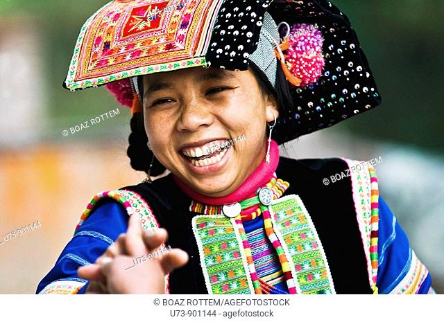 A beautiful young Yi woman laughs as she sees the camera