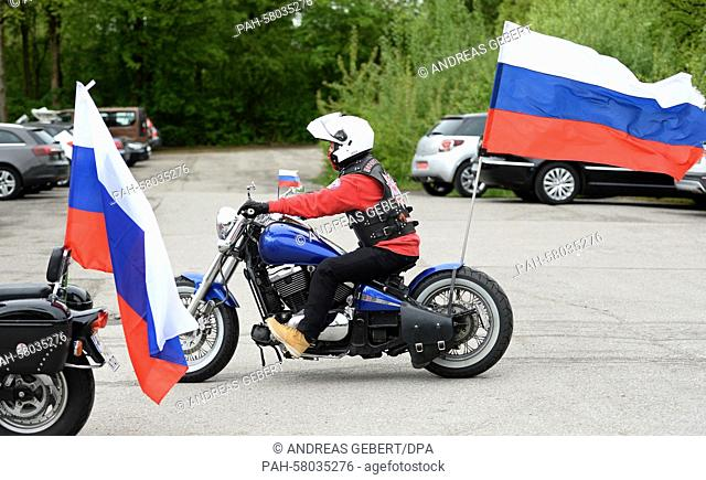 Supporters of the Russian bikers' club 'Night Wolves' carry Russian flags on their motobikes as they drives across the visitors' parking lot at the...