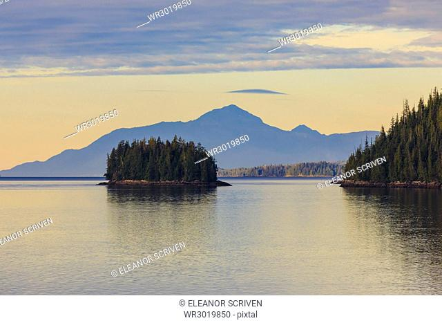 Sunrise, entering the Misty Fjords National Monument, islands, forest and distant mountains, Ketchikan, Southeast Alaska, United States of America